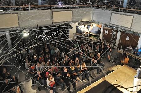 """Aula und auch die Ränge im Stock waren gut gefüllt. Die Zuschauer im ersten Stock mussten allerdings durch das """"Spinnennetz-Kunstwerk"""" blicken, das noch für die Lyrixx-Veranstaltung aufgebaut war."""